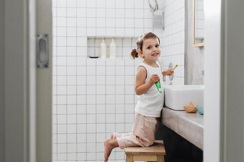 Kind verwendet Hocker, um an das Waschbecken zu gelangen